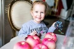 Błękitnooki śliczny dziewczyny obsiadanie przy stołem z jabłkami, wiśniami, winogronami i ono uśmiecha się, zdjęcia royalty free