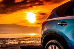 Błękitny ścisły SUV samochód z sportem i nowożytnym projektem parkującymi na betonowej drodze morzem przy zmierzchem Ekologicznie Obraz Stock