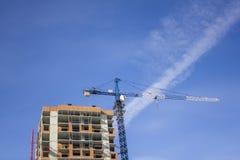 Błękitny basztowy żuraw blisko wysokiego budynku w budowie na tle jasny niebo zdjęcia stock