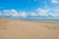 Błękitny chmurny niebo nad piasek plażą wzdłuż morza Zdjęcie Stock