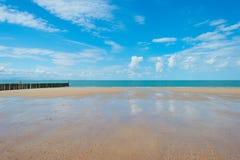 Błękitny chmurny niebo nad piasek plażą wzdłuż morza Zdjęcia Stock