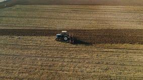 Błękitny ciągnik kultywuje brąz ziemię w Pogodnej wiośnie, jesieni pogoda zdjęcie wideo