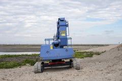 Błękitny ciągnik przy markierem Wadden z błękitnym chmurnym niebem, obrazy stock