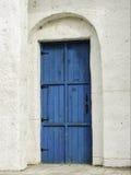 Błękitny drewniany drzwi na białej fasadzie Obrazy Stock