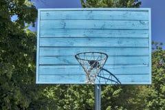 B??kitny drewniany koszyk?wki backboard w parku w?r?d lipowych drzew fotografia stock