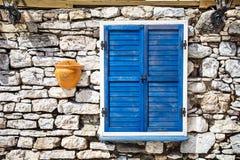 Błękitny drewniany okno na kamiennej ścianie Obrazy Royalty Free