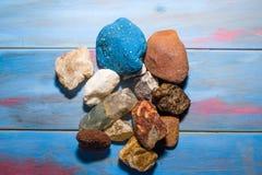 Błękitny drewniany tło z kamieniami różni kolory i tekstury zdjęcie royalty free