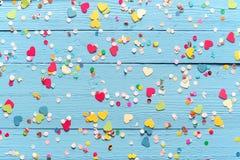 Błękitny drewniany tło z rozrzuconymi partyjnymi confetti Obrazy Stock