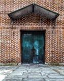 BÅ'Ä™kitny drzwi na czerwonej Å›cianie z cegieÅ' zdjęcie royalty free
