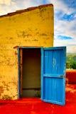 Błękitny drzwi otwiera na kolor żółty ścianie na czerwień dachu tarasie Obrazy Royalty Free