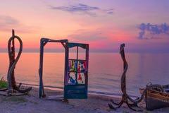 Błękitny drzwi z kolorowym szkłem i kotwicami na plaży przy wschodem słońca obrazy stock