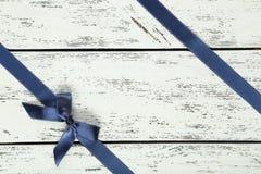 Błękitny faborek z łękiem na białym drewnianym tle Obrazy Stock