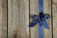 Błękitny faborek z łękiem na popielatym drewnianym tle Fotografia Royalty Free