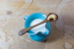 Błękitny handmade ceramiczny miotacz nerkodrzewu mleko, drewniana łyżka z pojedynczym nerkodrzewem balansował na wierzchołku fotografia stock
