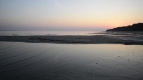 Błękitny i pomarańczowy niebo tuż przed wschód słońca odbijał na mokrym plażowym piasku z przybywającymi ocean fala zbiory