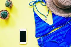 Błękitny koloru swimwear z smartphone, kaktusa i kapeluszu mieszkaniem, kłaść na żółtym tle, wakacje Fotografia Royalty Free