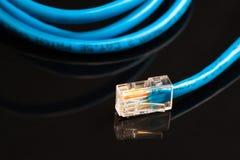 Błękitny komputerowy etherneta kabel odizolowywający na czarnym tle, zakończenie Fotografia Stock