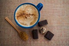 Błękitny kubek z kawą z mlekiem i cynamonem zdjęcie stock