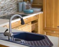 Błękitny kuchenny zlew i drewniani gabinety obraz stock