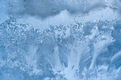 Błękitny marznący zimy okno z pięknym lodowatym wzorem Obrazy Stock