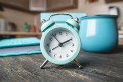 Błękitny metalu budzik na stole z kubkiem i dzienniczkiem na tle kuchnia Czas i domowy tryb zdjęcia royalty free