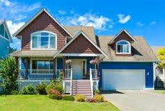 Błękitny mieszkaniowy dom z betonowym podjazdem w przodu i niebieskiego nieba tle fotografia stock