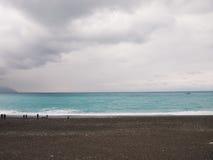 Błękitny morze i czarny piasek obraz stock
