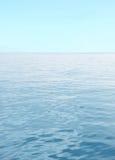 Błękitny morze z fala i jasnym niebieskim niebem Obrazy Stock