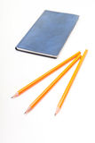 Błękitny notatnik i żółci ołówki na białym tle Obrazy Stock