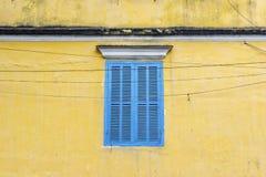 Błękitny okno na kolor żółty ścianie w Hoi Obraz Stock