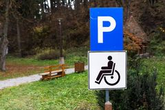 Błękitny parking znak dla niepełnosprawnych persons przy miasto parkiem zdjęcie royalty free