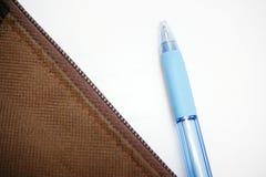 Błękitny pióro wziąć z brown torby na białym backgro Obraz Royalty Free