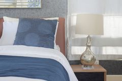 Błękitny pościel styl i klasyk stylowa biała czytelnicza lampa w sypialni zdjęcie stock