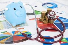 Błękitny prosiątko bank, stetoskop sprawdza stertę pieniądze monety i Obraz Stock