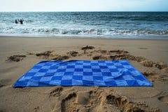 Błękitny ręcznik na piaskowatej plaży Obrazy Royalty Free