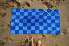 Błękitny ręcznik na piaskowatej plaży Obrazy Stock