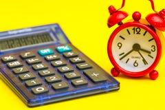 Błękitny rewolucjonistka budzik na kolorze żółtym i kalkulator Obrazy Royalty Free