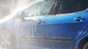 Błękitny samochód myjący ręką używać wodnego strumienia obmycie w błyszczącym dniu zbiory