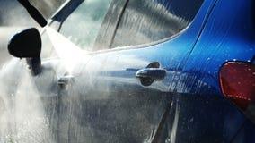 Błękitny samochód myjący ręką używać wodnego strumienia obmycie w błyszczącym dniu zdjęcie wideo