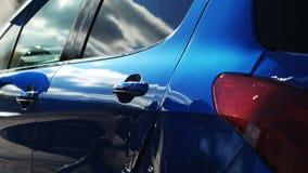 Błękitny samochód myjący ręką używać wodnego strumienia obmycie w błyszczącym dniu zbiory wideo