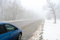 Błękitny samochód na mgłowej drodze Obrazy Stock