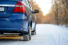 Błękitny samochód z zim oponami na Śnieżnej drodze Prowadnikowa skrytka Fotografia Stock