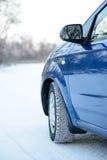 Błękitny samochód z zim oponami na Śnieżnej drodze Prowadnikowa skrytka Zdjęcie Royalty Free