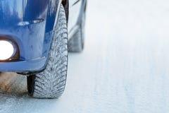 Błękitny samochód z zim oponami na Śnieżnej drodze Prowadnikowa skrytka Zdjęcie Stock
