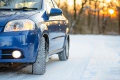 Błękitny samochód z zim oponami na Śnieżnej drodze Prowadnikowa skrytka Zdjęcia Stock