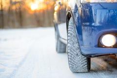 Błękitny samochód z zim oponami na Śnieżnej drodze Prowadnikowa skrytka Zdjęcia Royalty Free
