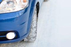 Błękitny samochód z zim oponami na Śnieżnej drodze Prowadnikowa skrytka Przestrzeń dla teksta Fotografia Stock