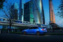 Błękitny samochodu pobyt na drogowym pobliskim mieście przy zmierzchem fotografia royalty free