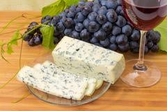 Błękitny ser przeciw czerwonemu winu i winogrona zakończeniu obrazy stock
