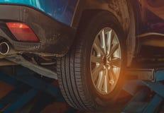 Błękitny SUV samochód parkujący w garażu warsztacie podnosi, odmieniania utrzymanie i opona i Auto poważny interes automobilowego fotografia royalty free